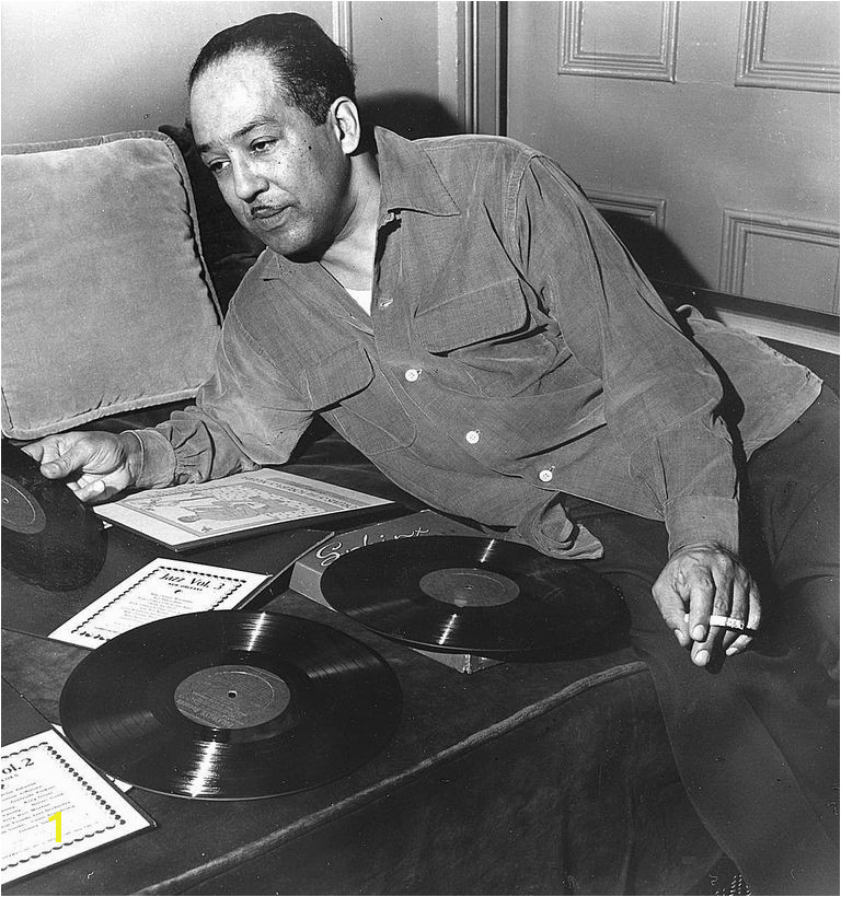 Langston Hughes leaning over records on a couch