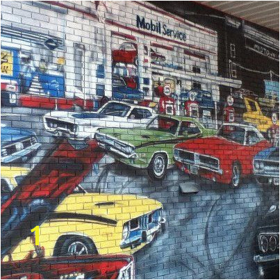 This wall mural is a tribute to the age of muscle cars and features a classic Challenger among some fast pany