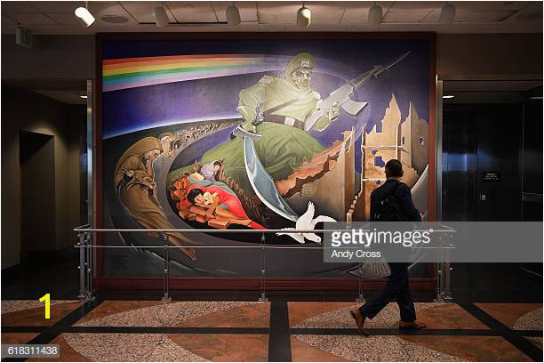 A traveler looks over a wall mural part of an installation at the Denver International Airport