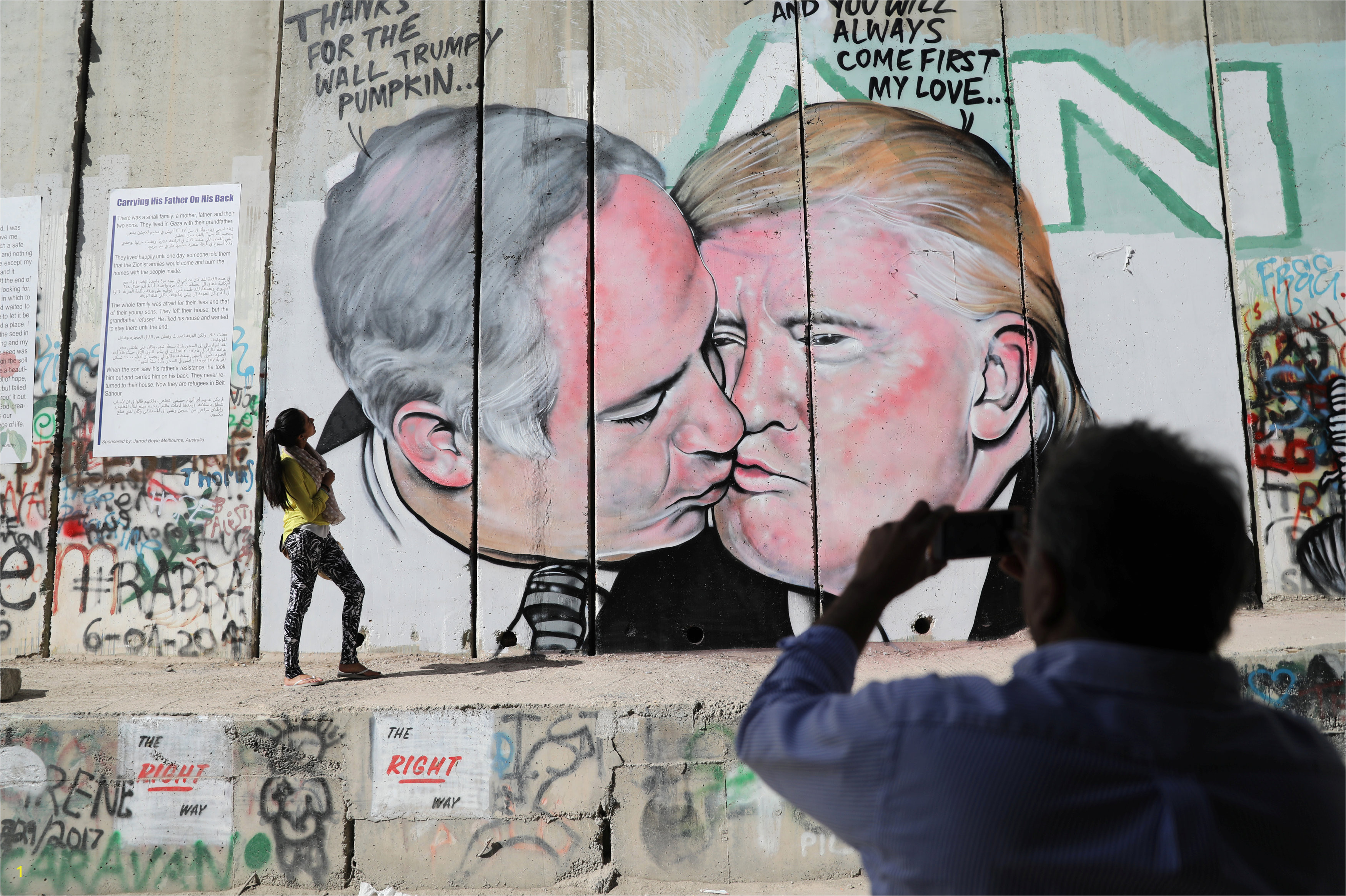 A man photographs a woman as she stands next to a mural depicting U S President Donald