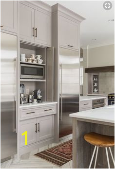 Gorgeous white and gray kitchen features two recessed stainless steel refrigerators flanking gray shaker cabinets fitted with aged brass pulls and folding