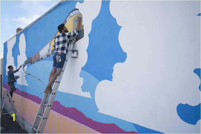Artists painting mural wall