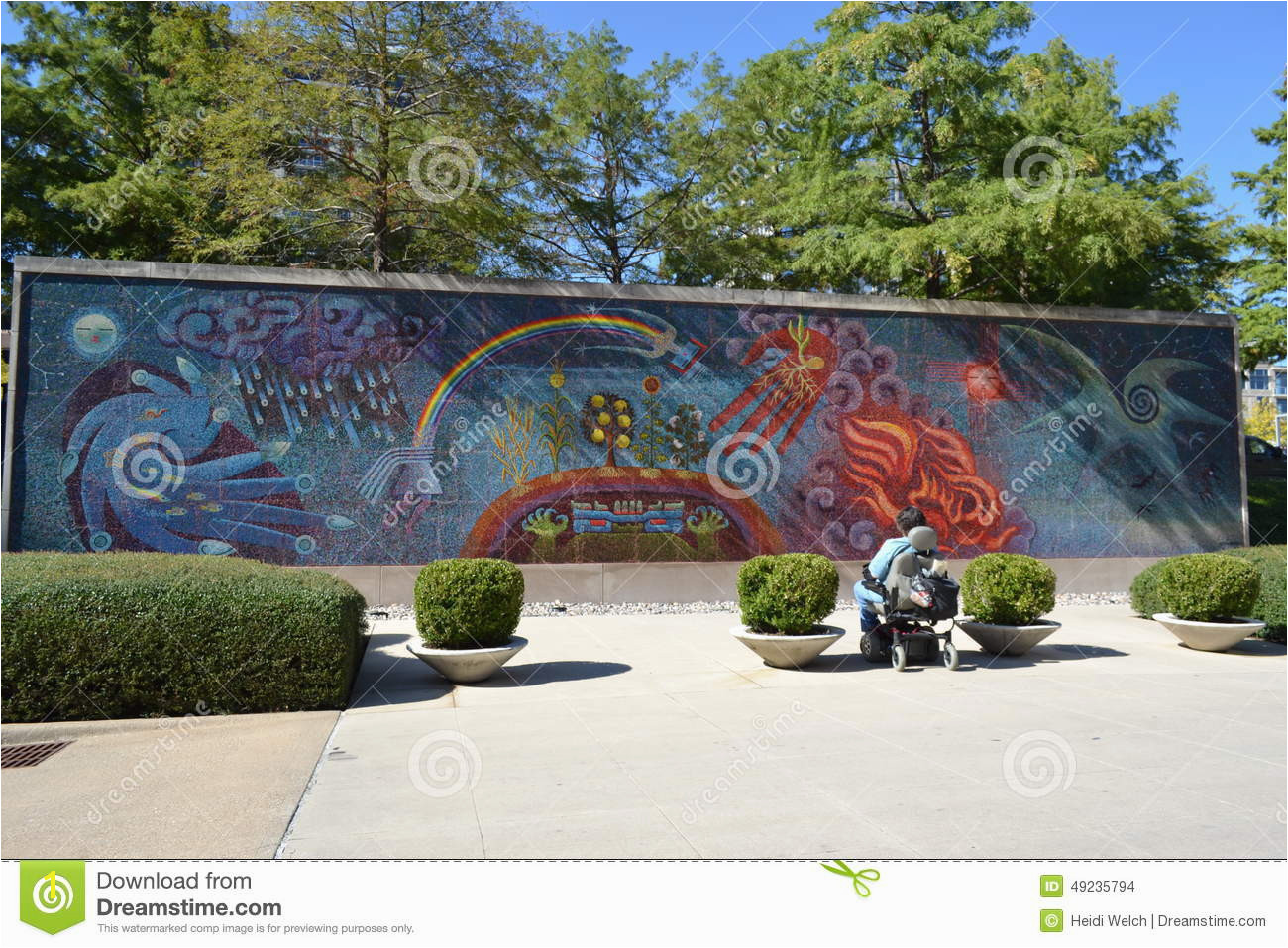Looking at a mural painted on a wall outside the Dallas Museum of Art one person in a wheelchair can be seen studying the mural