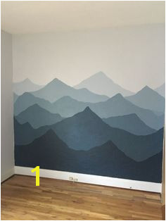 Painted a mountain mural in our nursery Used sherwin Williams Rock Candy and Sea Serpent With golden rays