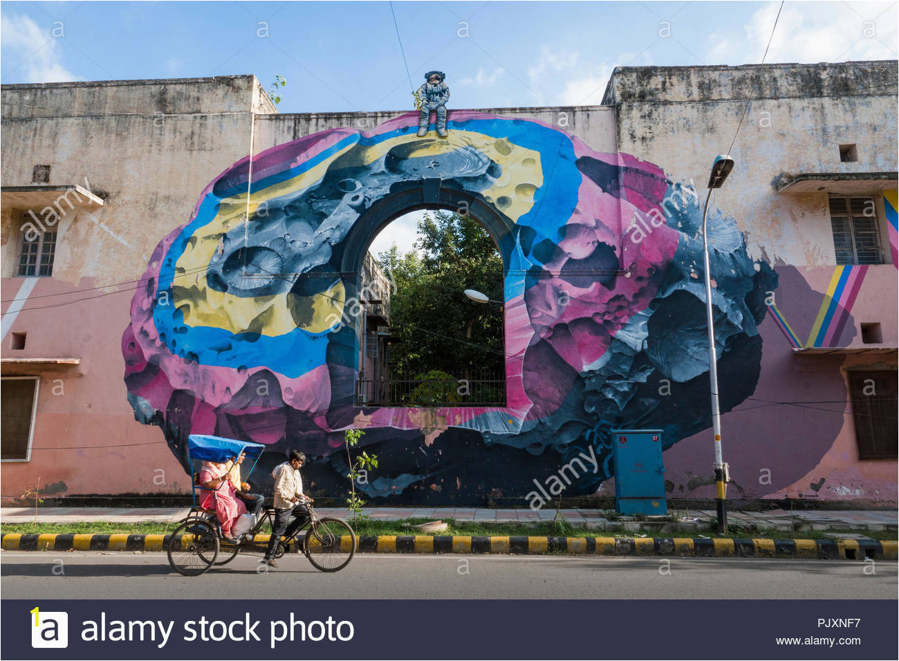 rickshaw rider and passenger ride past wall mural on building painted by swiss artists nevercrew in lodhi colony new delhi india PJXNF7
