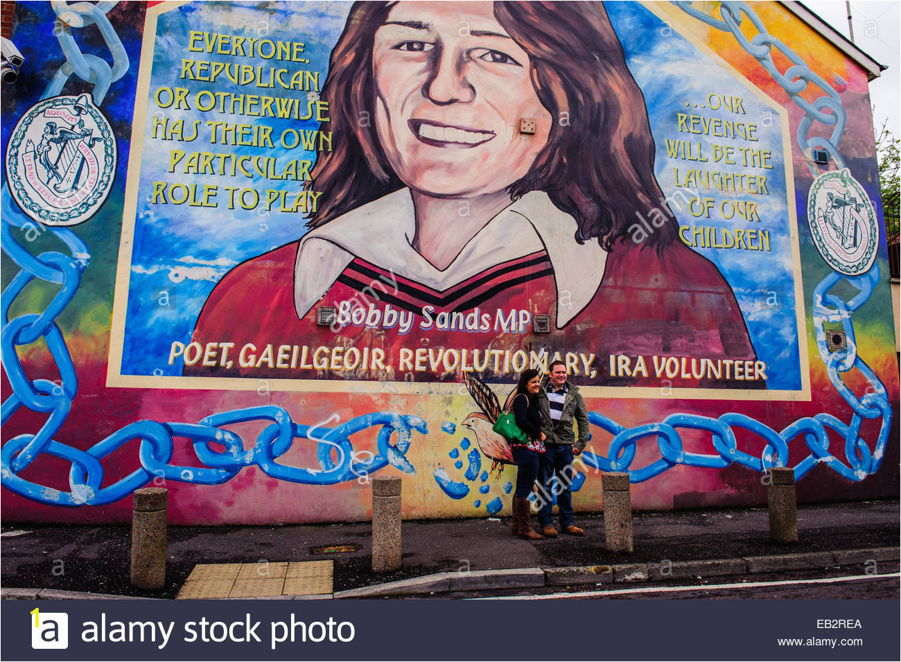 a couple poses in front of the bobby sands mural on the gable wall EB2REA