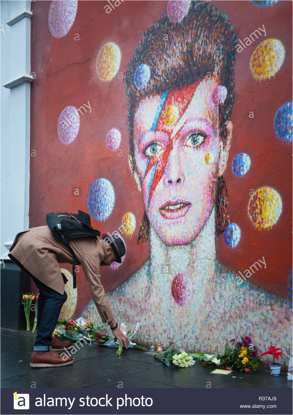 tunstall road london uk 11th january 2016 london uk mourners lay flowers at the foot of the david bowie mural in brixton pictured a man lay R37AJ9