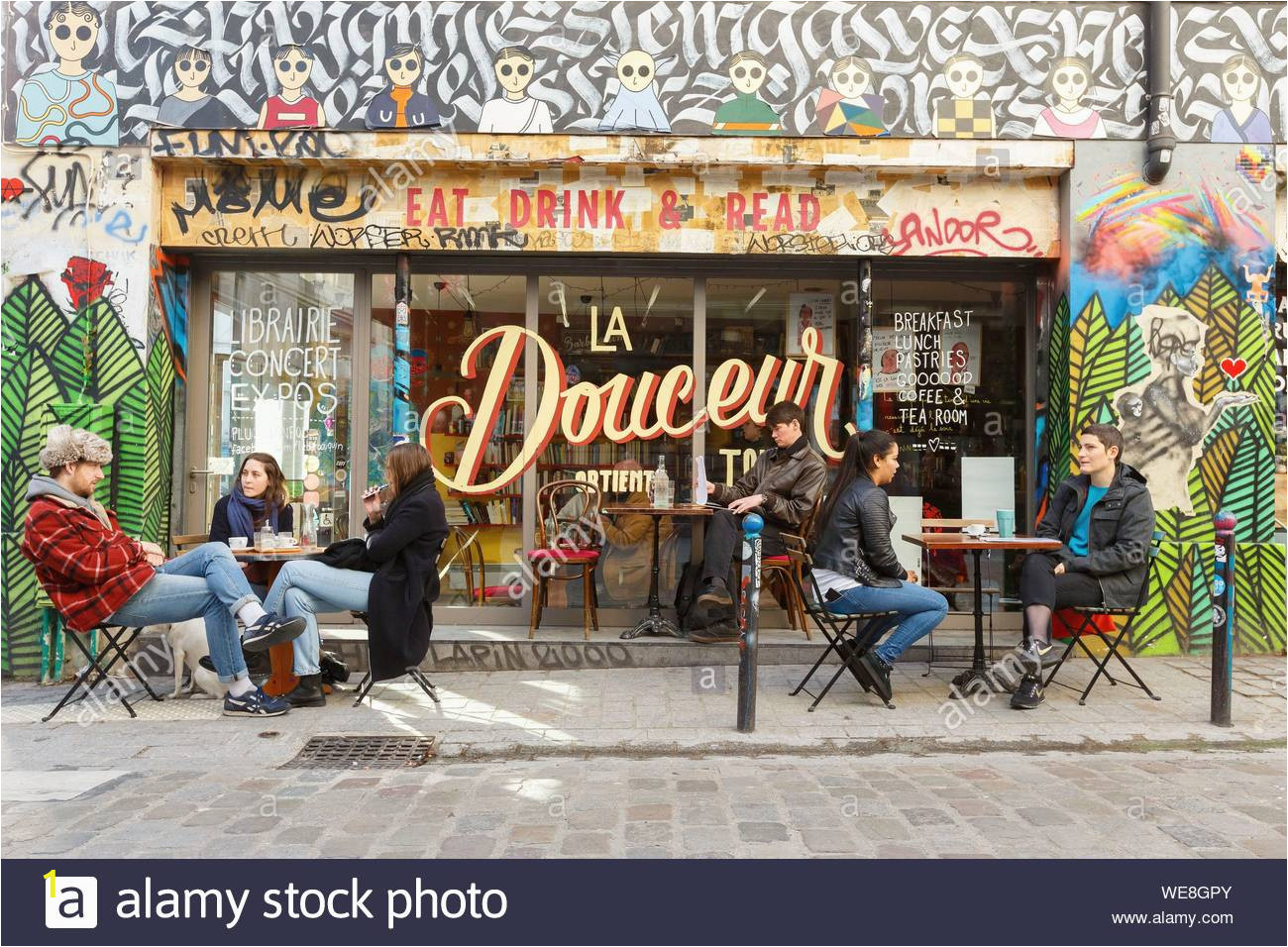 france paris street art graffitis and murals in rue denoyez the terrace of the barbouquin cafe and bookstore WE8GPY