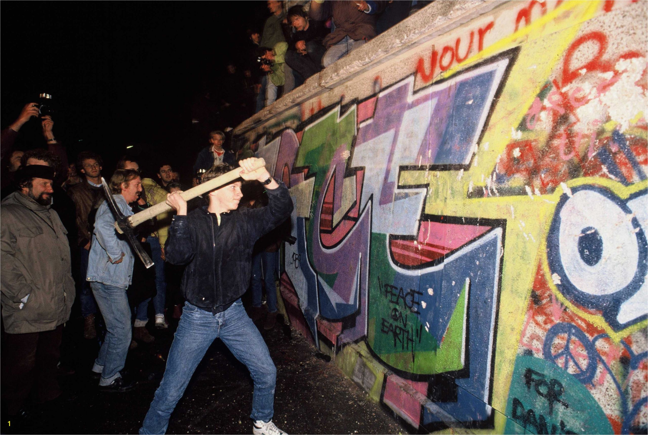 a man s the berlin wall with a pickaxe on the night of november 9th 1989 5c4bd496c9e77c0001d7b994