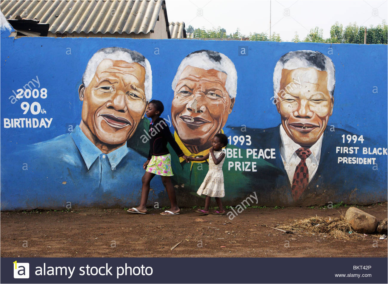 children passing a nelson mandela wall mural in the township soweto BKT42P