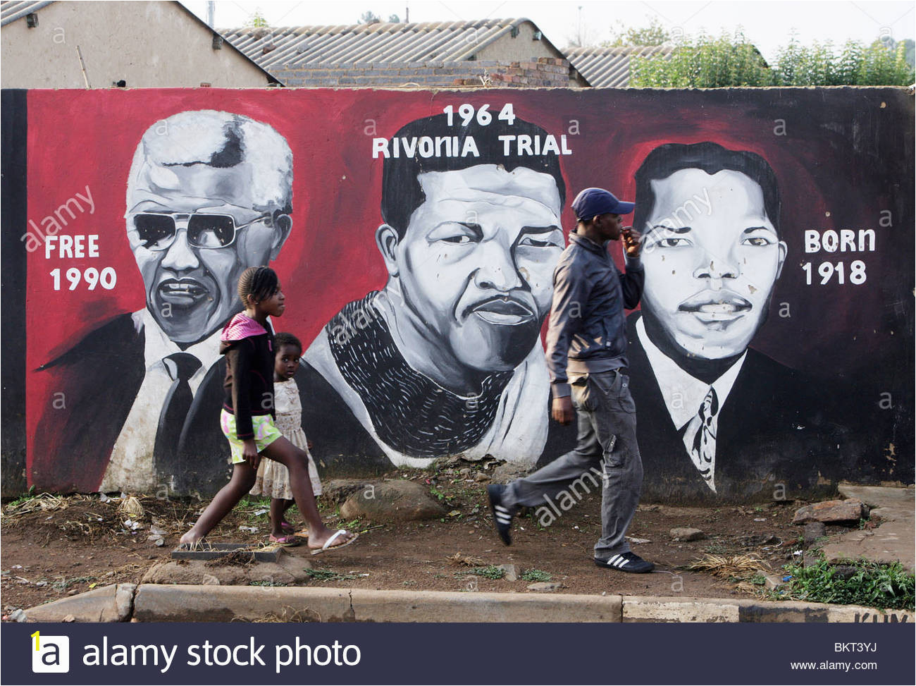 children passing a nelson mandela wall mural in the township soweto BKT3YJ
